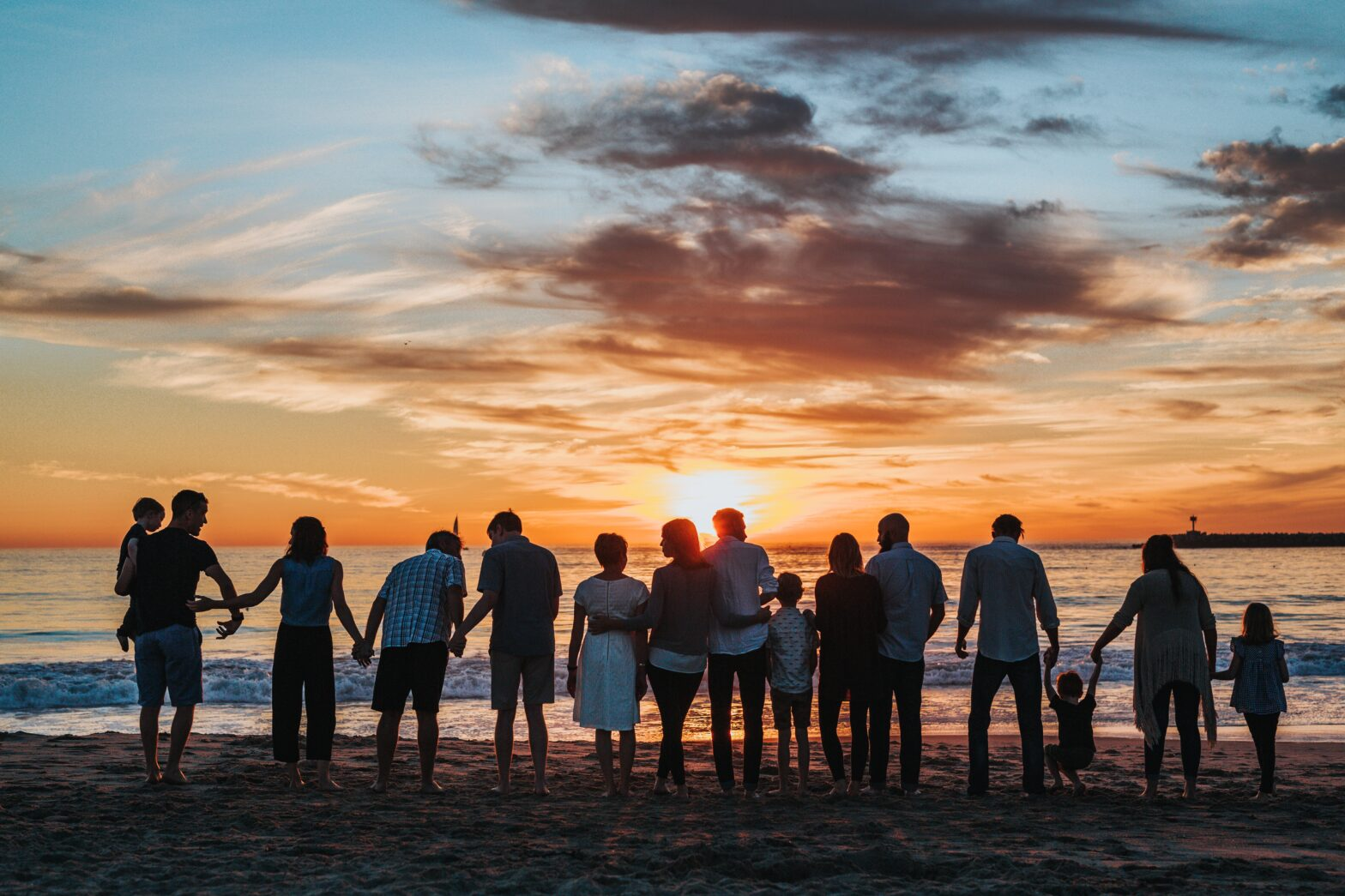 Friends and family on a beach at sunset.